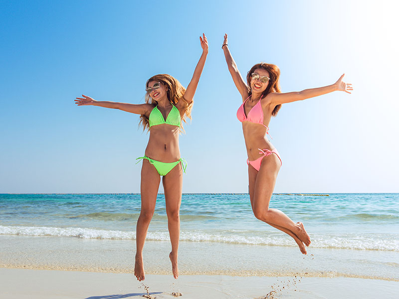 Happy bikini two asian women jumping of joy and success on perfect white sand beach on caribbean tropical vacation. Holiday girls with sexy slim suntan body running of freedom and happiness.